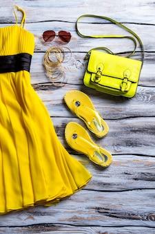 Gelbes kleid mit limetten-geldbörse. handtasche, flip-flops und kleid. der trendige sommerlook der lady. bunte kleidung auf dem display.