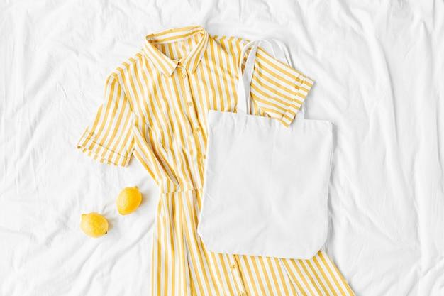 Gelbes kleid mit streifen mit öko-tasche auf weißem bett. stylisches sommeroutfit für damen. trendige kleidung mit weißem öko-taschenmodell. flache lage, ansicht von oben.