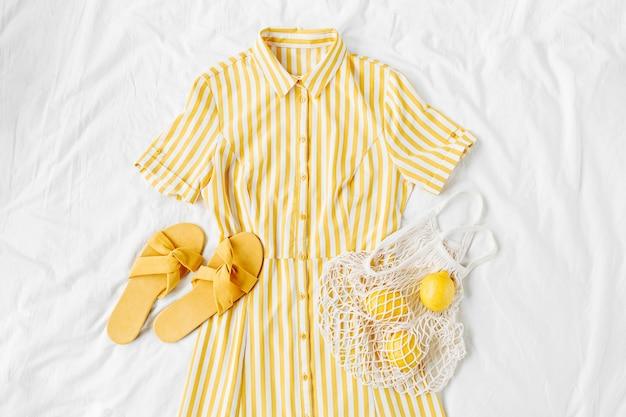 Gelbes kleid mit streifen mit öko-tasche und hausschuhen auf weißem bett. stylisches sommeroutfit für damen. trendige kleidung. flache lage, ansicht von oben.