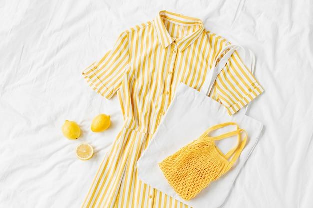 Gelbes kleid mit streifen mit öko-tasche und zitronen auf weißem bett. stylisches sommeroutfit für damen. trendige kleidung. flache lage, ansicht von oben.