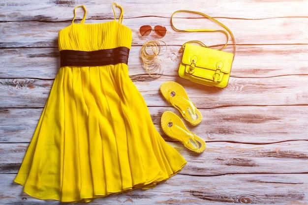 Gelbes kleid, sonnenbrille und tasche. lässiges kleid mit hellen accessoires. sommer-outfit-idee für mädchen. modische kleidung auf lager.