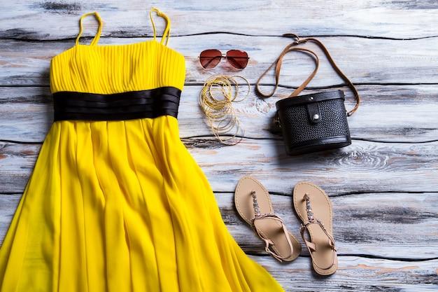 Gelbes kleid und beige sandalen. sandalen, kleid und schwarze handtasche. stilvolles kleid mit klassischer handtasche. damen-outfit mit dunklem accessoire.