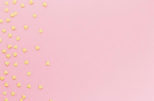 Gelbes konfetti in form von herzen auf einem rosa hintergrundkopienraum