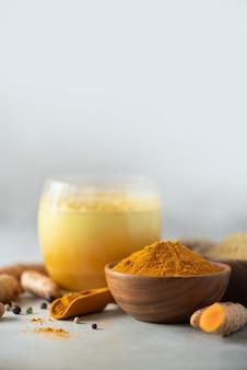 Gelbes kurkuma-latte-getränk. goldene milch mit zimt, gelbwurz, ingwer über grauem hintergrund. platz kopieren.