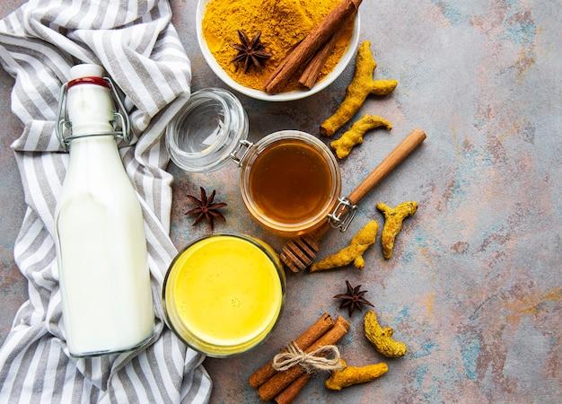 Gelbes kurkuma-latte-getränk. goldene milch mit zimt, kurkuma, ingwer und honig über betonhintergrund.