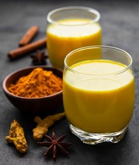 Gelbes kurkuma-latte-getränk. goldene milch mit zimt, kurkuma, ingwer und honig über schwarzer steinoberfläche.