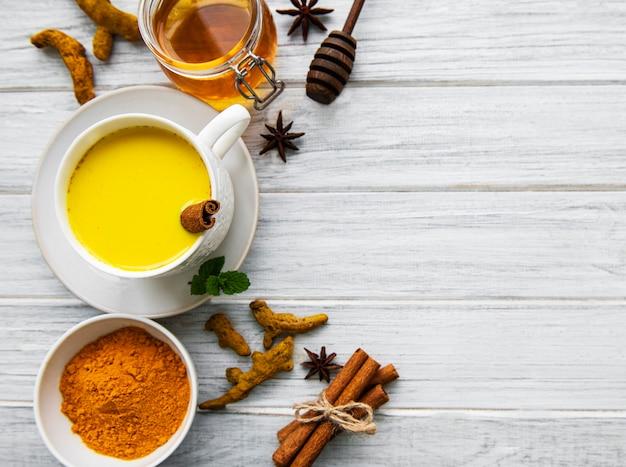 Gelbes kurkuma-latte-getränk. goldene milch mit zimt, kurkuma, ingwer und honig über weißer holzoberfläche.