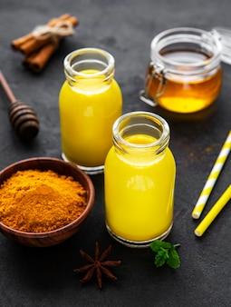 Gelbes kurkuma-latte-getränk. goldene milch mit zimt, kurkuma, ingwer und honig