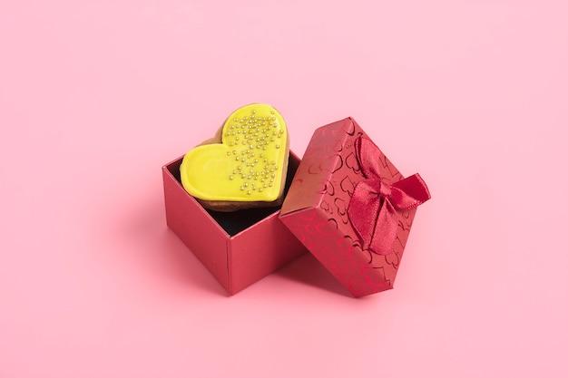Gelbes lebkuchenherz im roten kasten auf rosa hintergrund
