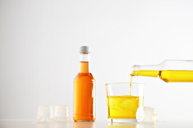 Gelbes leckeres limonadengetränk gießt von flasche zu glas mit eiswürfeln in der nähe der geschlossenen versiegelten unbeschrifteten flasche mit orangengetränk