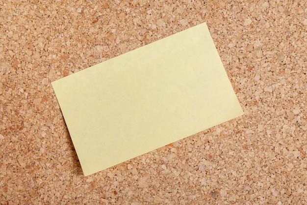 Gelbes leeres aufklebermodell mit festgestecktem korkbrett