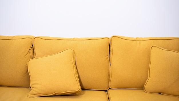 Gelbes leinensofa mit zwei kissen und weißer wand Premium Fotos