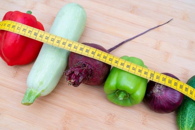 Gelbes maßband und gemüse auf einem holzbrett. gesunde lebensstil-diät.