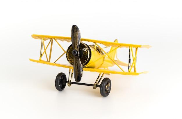 Gelbes metallspielzeugflugzeug der weinlese lokalisiert auf weiß
