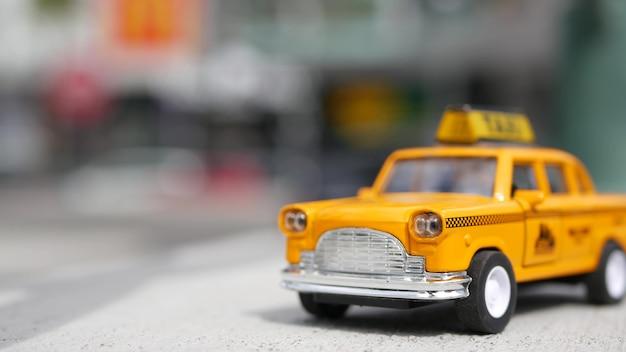Gelbes mini-taxi in den usa. kleines retro-automodell. kleines autospielzeug mit dame.