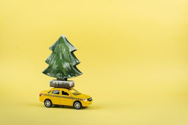 Gelbes miniaturtaxi, das einen weihnachtsbaum trägt