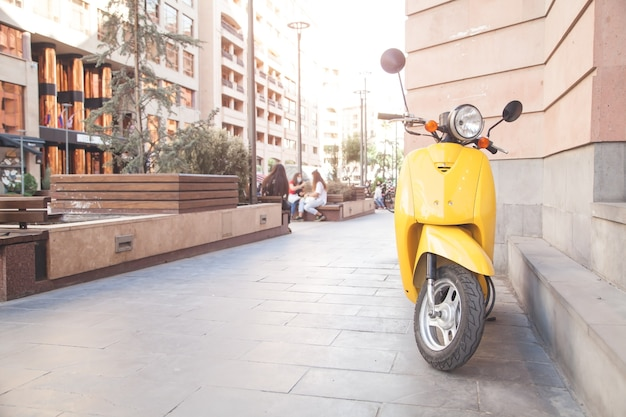 Gelbes modernes moped in einer stadt.