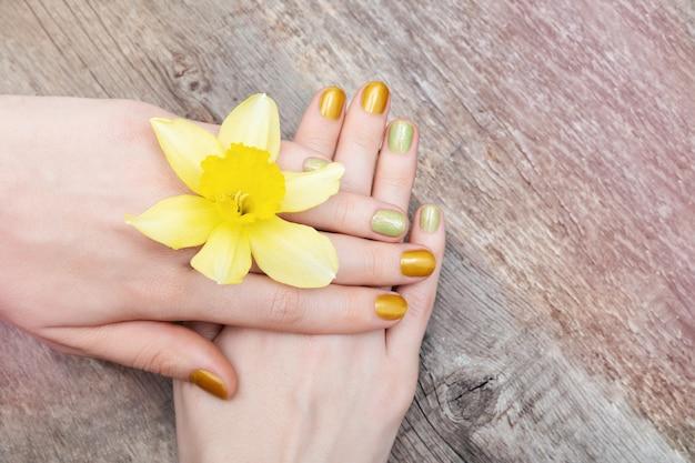 Gelbes nageldesign. weibliche hand mit glitzer-maniküre, die narzissenblüten hält.