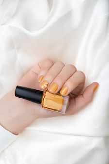 Gelbes nageldesign. weibliche hand mit glitzer-maniküre.