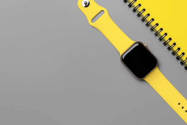 Gelbes natepad und intelligente uhr auf grauer draufsicht