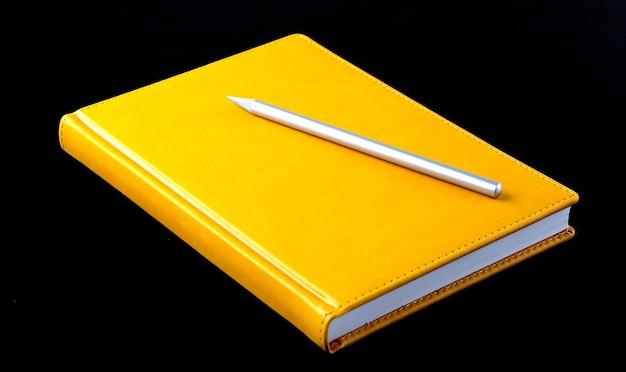 Gelbes notizbuch mit stift auf schwarzem hintergrund