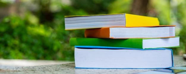 Gelbes, oranges, grünes, blaues buch auf den tisch gelegt. wissensbücher und bildungskonzepte.