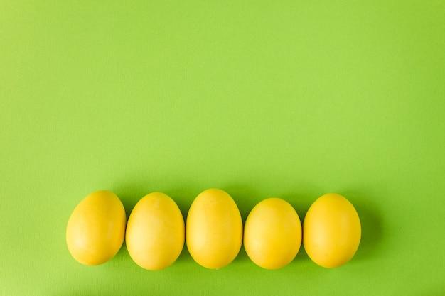 Gelbes osterei auf hellgrünem hintergrund