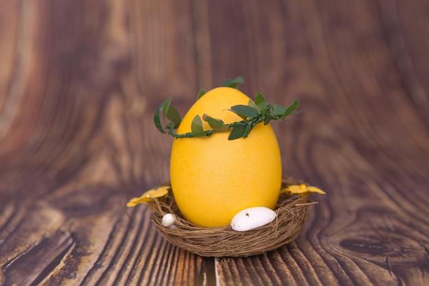 Gelbes osterei in einem nest auf hölzernem hintergrund