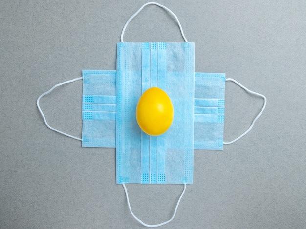Gelbes osterei liegt auf blauen medizinischen masken auf grauem hintergrund