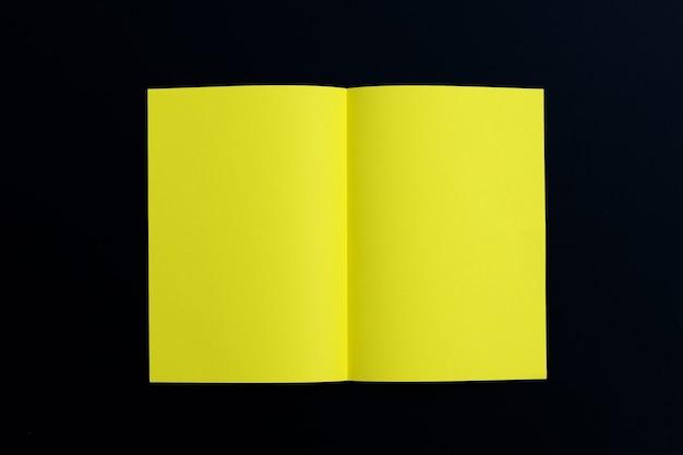 Gelbes papier auf dunkler oberfläche. draufsicht