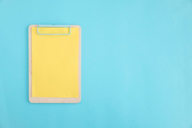 Gelbes papier auf hölzernem klemmbrett über dem blauen hintergrund