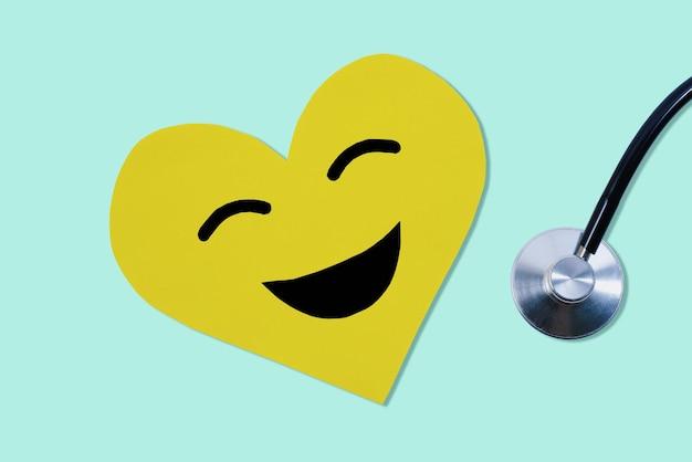 Gelbes papier geschnittenes herz-smiley-gesicht und kardiogramm-instrument auf pastellgrünem hintergrund
