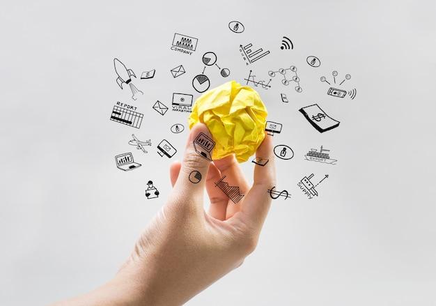 Gelbes papier zerknitterte kugel auf menschlicher hand mit geschäftsikonen
