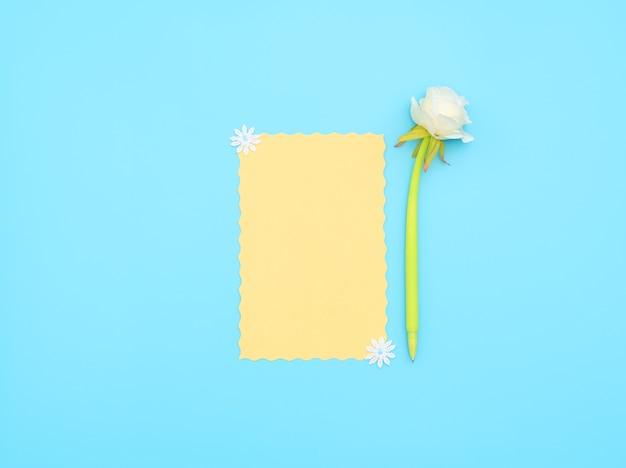 Gelbes papierblatt mit grünem stift mit weißer blume darauf auf blauem hintergrund