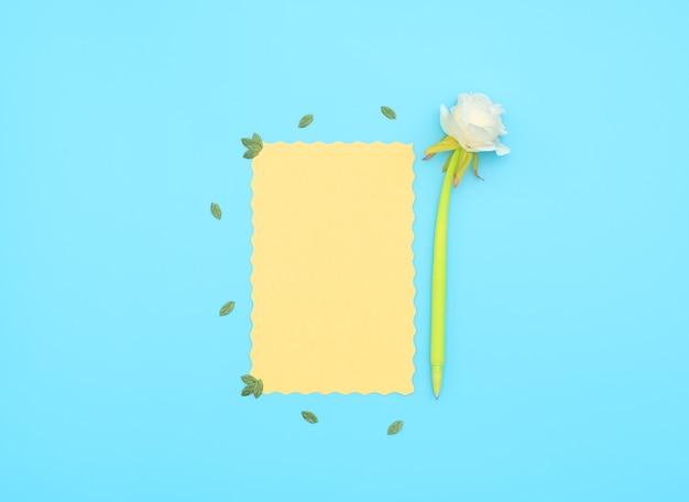 Gelbes papierblatt mit stift mit weißer blume darauf auf blauem hintergrund