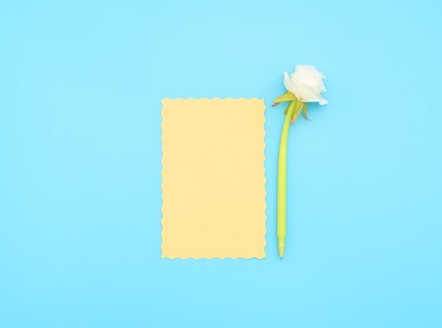 Gelbes papierblatt und grüner stift mit weißer blume darauf