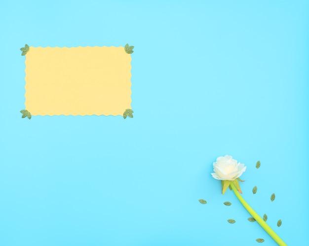 Gelbes papierblatt und weiße blume mit grünen blättern auf blauem hintergrund