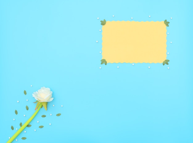 Gelbes papierblatt und weiße blume mit grünen blättern und perlen auf blauem hintergrund