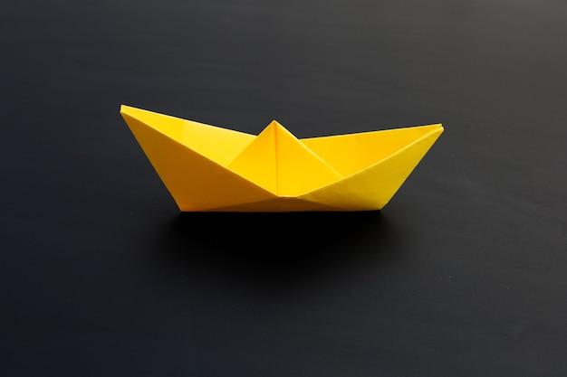 Gelbes papierboot auf dunkler oberfläche. speicherplatz kopieren