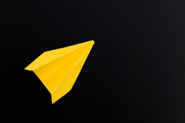 Gelbes papierflugzeug auf dunkler oberfläche. draufsicht