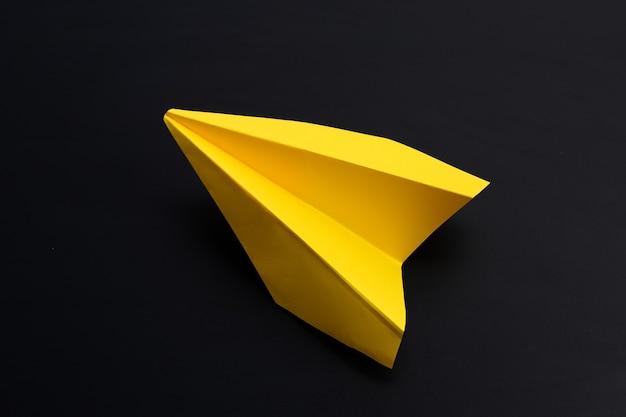 Gelbes papierflugzeug auf dunkler oberfläche.