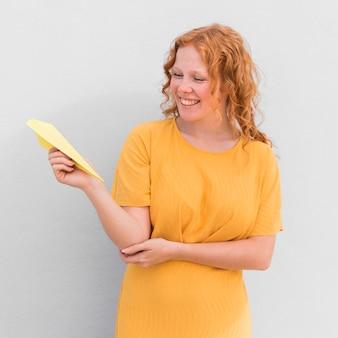 Gelbes papierflugzeug des glücklichen mädchens