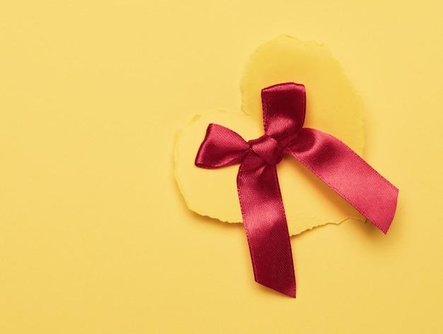 Gelbes papierherz und rote seidenschleife auf gelber oberfläche