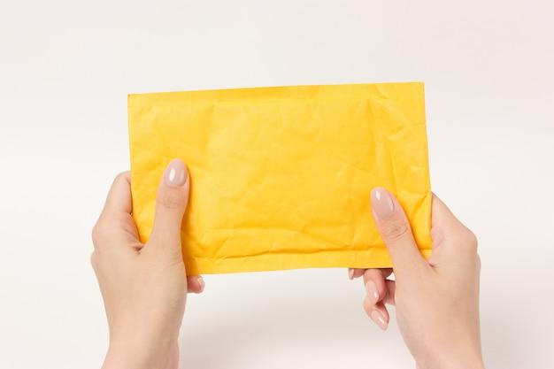 Gelbes postpaket, das weibliche hände hält