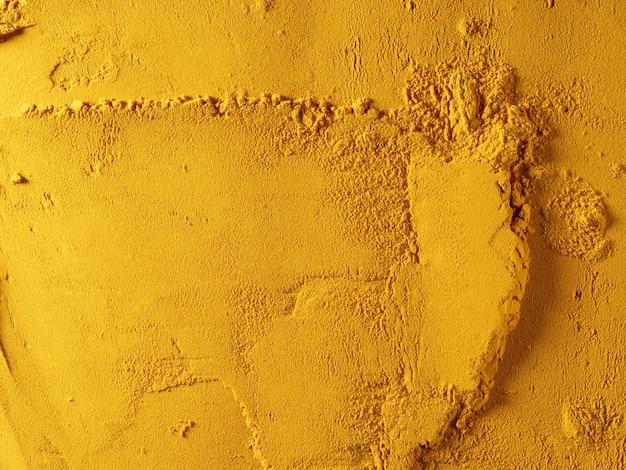 Gelbes pulver aus geriebenem kurkuma mit textur, lebensmittelhintergrund. von oben betrachten.