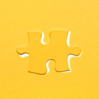 Gelbes puzzleteil über farbigem hintergrund