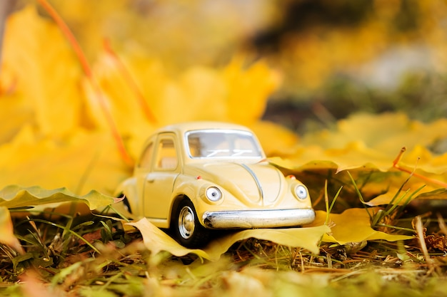 Gelbes retro- spielzeugauto auf herbstahornblatt. herbstreise und ferienkonzept.
