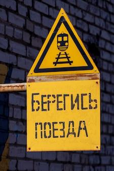 Gelbes schild mit einem bild des zuges. aufschrift in russischer sprache vorsicht vor dem zug. foto in hoher qualität