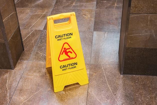 Gelbes schild warnt nassen boden mit einem fallenden mann im flur der öffentlichen toilette.