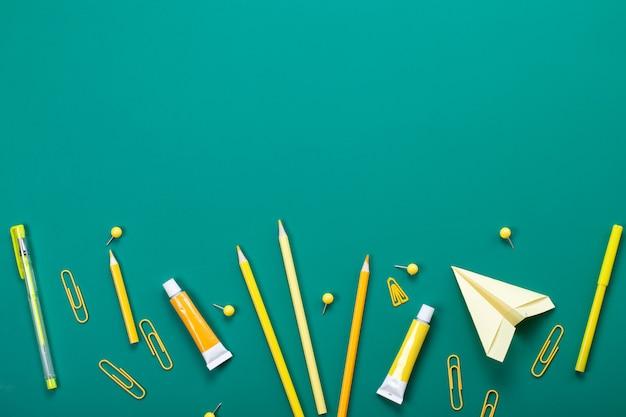 Gelbes schulmaterial über dem grünen brett. bildung, studing und back to school-konzept